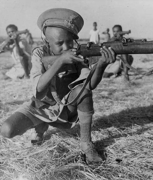 "Ethiopian Warriors Fighting for Liberty Aid British Troops: Among the Ethiopian warriors are fathers, sons, and brothers. A 14 year-old boy who have been wageing war against the Italians for 5 years. He is wearing the cap of an Italian officer sniped during one of his encounters with the enemy."" Source: British official photograph. No. BM 122º."