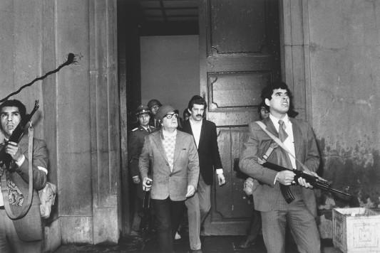 """Au centre, coiffé d'un insolite casque militaire, le président du Chili Salvador Allende fait une dernière sortie du Palais présidentiel de La Moneda, peu avant que l'aviation militaire ne commence son bombardement. Il tient dans la main un fusil d'assaut. À ses côtés, le médecin Danilo Bartulín, le commandant en chef des « Carabineros » José Muñoz (au fond à gauche) et des membre des GAP (Grupo de Amigos del Presidente). Quelques minutes plus tard, Salvador Allende se donne la mort avec l'arme offerte par Fidel Castro. L'image parut dans le New York Times grâce à un intermédiaire demeuré inconnu, obtint le World Press Photo en 1973 et fit dès lors le tour du monde. À la demande de son auteur, elle demeura anonyme jusqu'à sa mort en 2007. Le journal chilien """"La Nación"""" révéla alors qu'il s'agissait d'Orlando Lagos, photographe personnel de Salvador Allende lors de ses quatre campagnes présidentielles et durant ses trois années à la tête du Chili. Le quotidien new-yorkais ne lui paya jamais ce reportage, qu'il parvint à cacher sur lui pendant une courte trêve où il put quitter le Palais assiégé et partir en exil, ainsi que les filles d'Allende."""