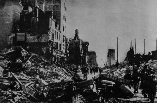"""Rue de Paris. Immédiatement après le bombardement, les rescapés sauvent ce qu'ils peuvent et partent à la recherche d'un refuge. Photo: W. Beaufils. InPierre Aubery, """"le siège et la bataille du Havre (1er au 12 septembre 1944) d'après des documents anglais"""", in Études normandes, Livraison 12 N°39 3 trimestre 1954 ."""