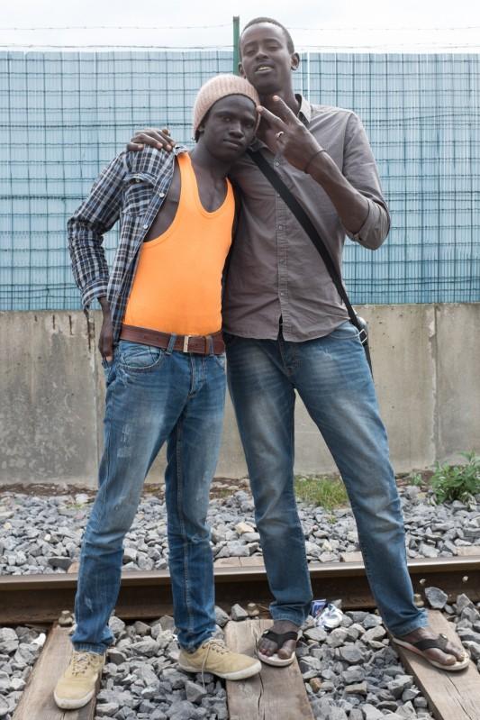 """Calais, 4 juillet 2014.  Mounir et Mohammed ont  20 et 17 ans. Ils viennent du Soudan. Ils marchent sur une voie de chemin de fer à l'abandon, de retour d'une """"jungle"""" lointaine vers les marges du centre-ville."""