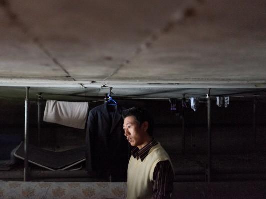 Sous le pont, dans l'un des rares endroits où l'on peut tenir debout, un réfugié écoute un membre du groupe interrogé par RFI.  Octobre 2014. Photo: Olivier Favier.