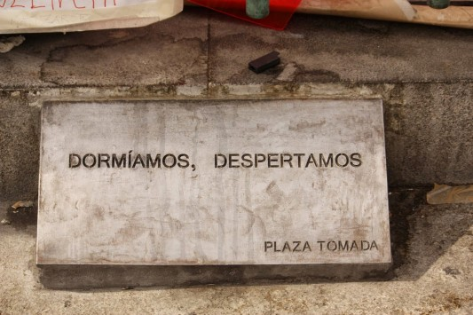 Dalle apposée au monument au centre de la Puerta del Sol durant l'acampada. On lit : « Nous dormions, nous nous réveillons » et dans le coin en bas « Place prise ». © Hedwig Marzolf et Ernesto Ganuza.