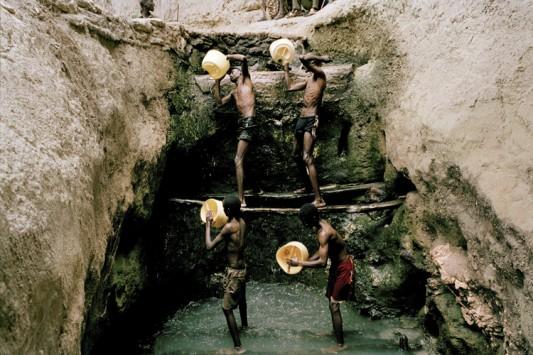 """Des bergers Borana puisent l'eau au rythme des chants traditionnels. Les """"puits chantants"""" sont des cavités creusées dans la roche il y a des centaines d'années. On y a recours quand les eaux de surface sont totalement épuisées. Photo: Claudio Sica."""