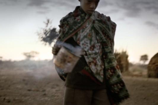 Un jeune porte une tasse de lait à peine trait dans son habitation. Photo: Claudio Sica.