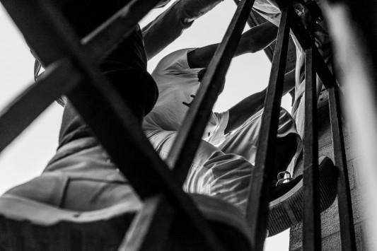 Après la fermeture du Bois Dormoy, migrants et soutiens se dirigent vers une ancienne caserne de pompiers en partie désaffectée. Dehors, d'autres migrants et des militants tentent de rejoindre les occupants en escaladant les murs, à leurs risques et périls. Les CRS chargent, dans la panique, une jeune femme fait une chute de deux mètres, heureusement sans conséquence. Juin 2015. Photo: Olivier Favier.
