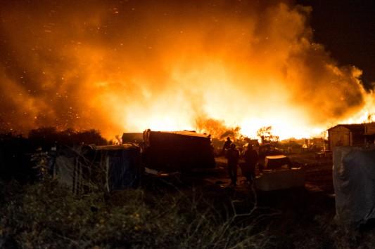 Munis de lampes-torches, les CRS entrent dans la zone incendiée, à la recherche d'éventuelles victimes, ou de personnes revenues sur les lieux à la recherche d'effets personnels. Les pompiers arriveront bien plus tard. Photo: Olivier Favier.