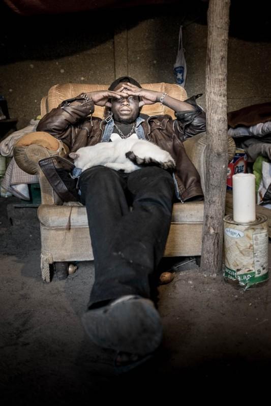 Dans la tente des Soudanais, où Adam et ses amis se réunissent souvent car c'est un des rares lieux confortables du secteur, un chat a élu domicile. Il occupe le seul fauteuil et personne n'ose le lui disputer, sinon le temps d'un portrait. Photo: Olivier Favier.