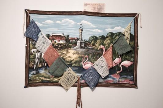 Sur le mur d'une chambre, le résumé d'un voyage: des drapeaux de prière tibétains, un billet de banque indien, un paysage de France.